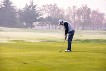 Golfer Playing Golf On The Golf Course During A Winter Day
