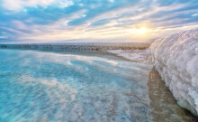 Sand Completely Covered With Crystalline Salt Looks Like Ice Or Snow On Shore Of Dead Sea, Turquoise Blue Water Near, Sky Colored With Morning Sun Distance - Typical Scenery At Ein Bokek Beach, Israel