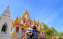 Couple Impressed By The Amazing Loha Prasat (Iron Castle) Which Adorned With 37 Golden Spires Inside Wat Ratchanatdaram Temple, Bangkok Old City, Thailand