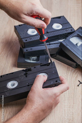 A man takes apart an old videotape and uses a screwdriver to unscrew the bolts from the case Fototapet