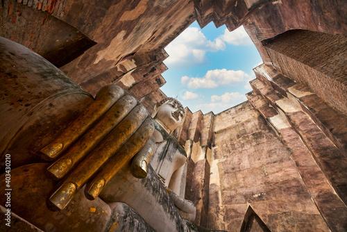 Obraz na plátně Giant buddha sculpture in old history wat sri chum sukhothai and blue sky