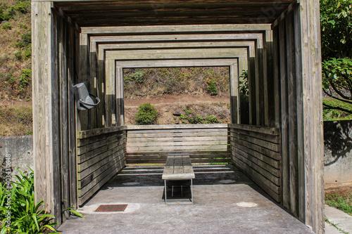 Un puente en las sobre un rio de agua dulce con bancos de madera y un arboles de hojas verdes