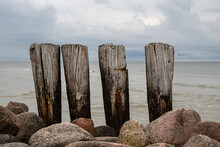 Pillars Made Of Aged Wood - The Remains Of An Old Pedestrian Bridge On The Shores Of The Baltic Sea