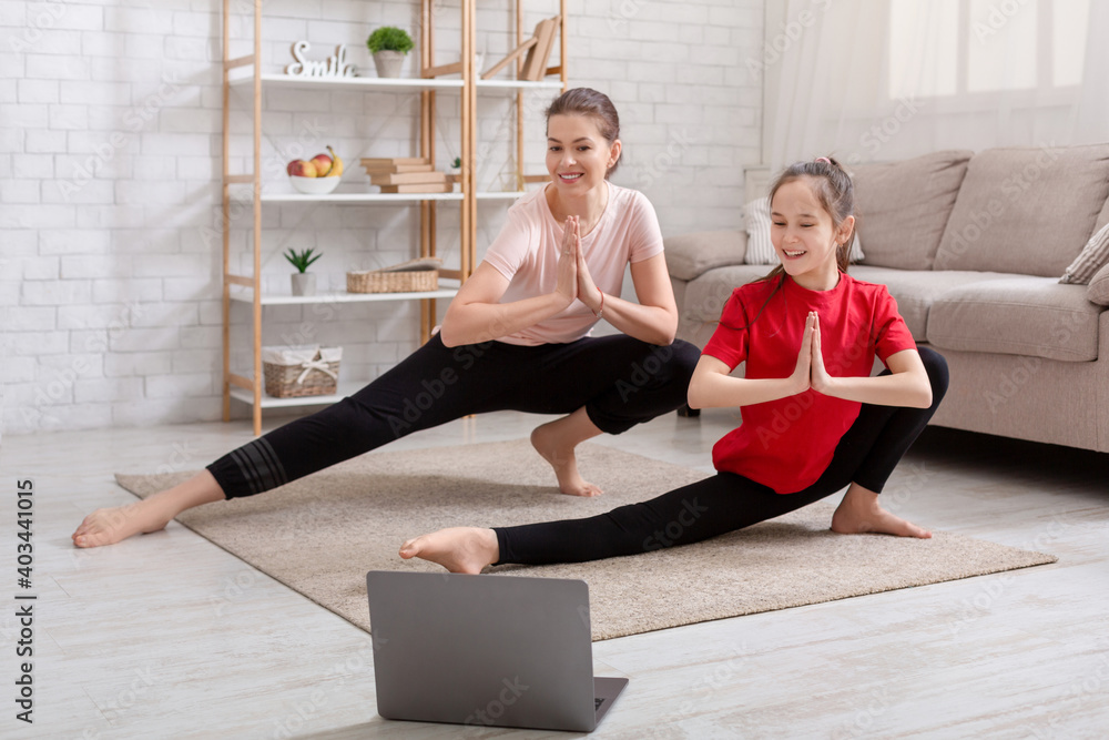 Fototapeta Happy millennial mother and her teenage daughter watching online sports video tutorial, doing exercises on floor at home