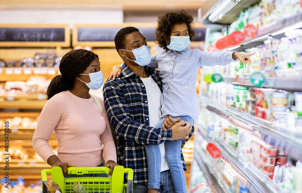 Fototapeta Family shopping during coronavirus pandemic. Black family with child wearing face masks, purchasing food at supermarket