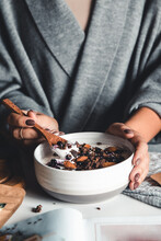 Closeup Of Bowl With Fresh Oatmeal And Spoon In Woman Hands, Healthy And Nutritive Breakfast Concept. Unrecognizable Lady Holding Delicious Homemade Granola, Having Breakfast At Home