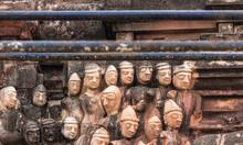 Hampi, Karnataka, India - November 5, 2013: Sri Krishna Temple In Ruins. Closeup Of Group Of Sculpted Beige Male Faces Against Molded Wall Under Iron Bars.