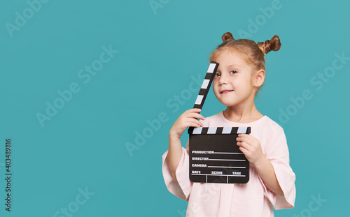 Fotografie, Obraz Funny smiling child girl hold film making clapperboard isolated on blue background