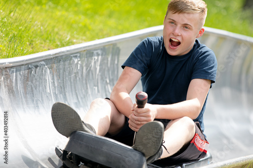 Fotografering Happy teen boy riding at bobsled roller coaster rail track in summer amusement p