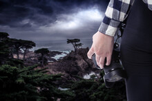 Female Photographer Or Tourist With A Photography Hobby Looking At The Ocean Landscape Of The California Coastline.  It Is Cloudy And There Is A Coming Storm