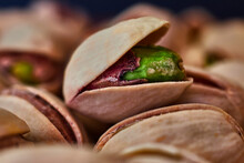 Close-up Of Green Pistachio With Open Shell, Next To More Pistachios