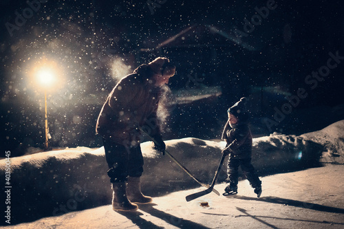 Canvas Print Father is teaching his little son to play hockey at night during the snowfall under the light of the lantern in Russia