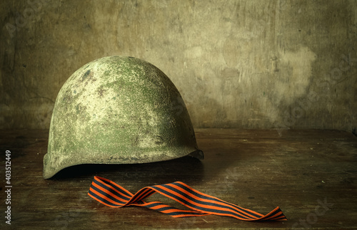 Fototapeta Helmet of a Soviet soldier during the war, green on a wooden table, next to the St