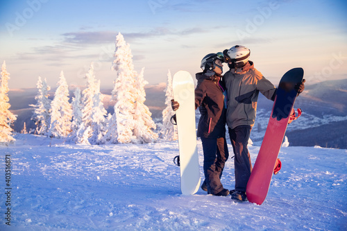 Fototapeta Loving couple of snowboarders woman and man hugging on top of mountain, concept