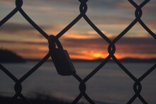 Padlock On A Chainlink Fence At Sunset
