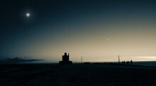 Greyscale Photo Of A Lighthouse Overlooking The Ocean On A Winter's Night. With A Crescent Moon And Aeed Bright Star.