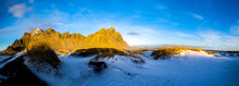 Wide Angle View Of Jagged Vestrahorn Mountain In Iceland, With Snow-covered Sand Dues In The Foreground.