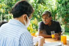 Grandfather Enjoy Orange Juice In Picnic Place Together.