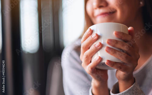Obraz Closeup image of a beautiful young asian woman holding and drinking hot coffee in cafe - fototapety do salonu