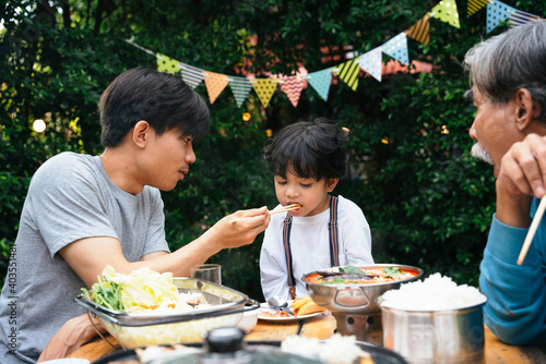 Asian daddy feeding food to son in dinning party outdoor. Wallpaper Mural