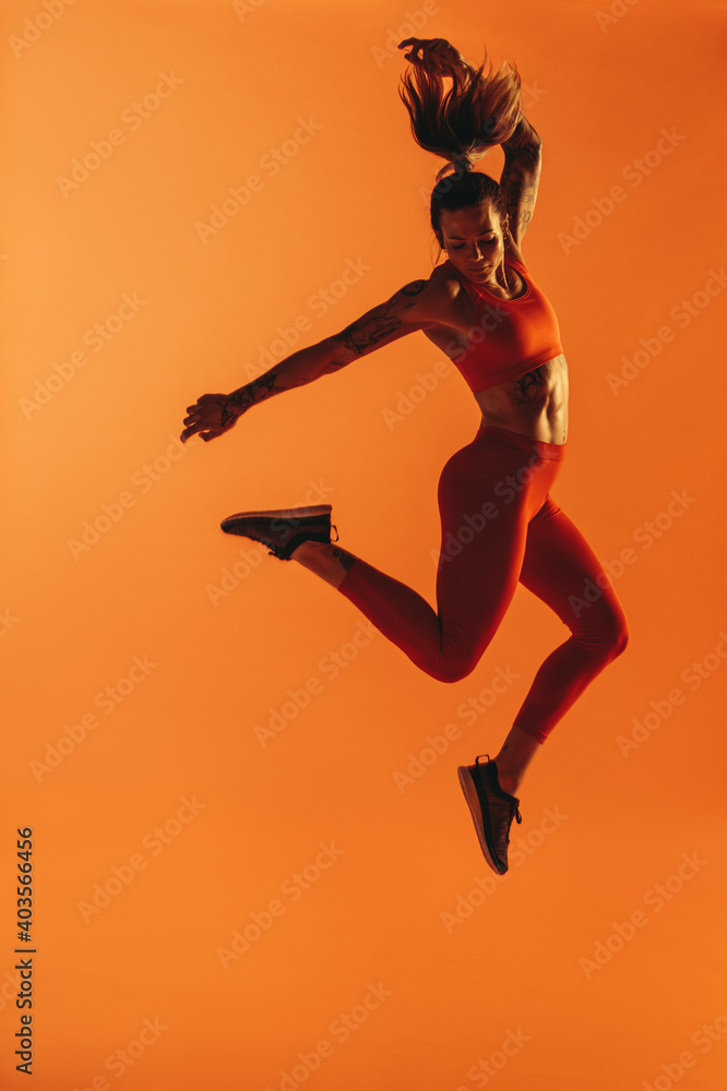 Fototapeta Portrait of fit woman jumping in air during workout