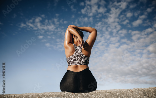 Fotografía Plus size woman sitting on wall and stretching arms