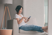 Work From Home Happy Asian Mature Woman Relaxing In Sofa Using Mobile Phone Online Shopping Or Remote Working.