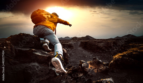 Fotografiet Successful man hiking mountains at sunset - Hiker with backpack pointing the sky