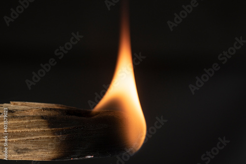 Foto macro shot of a piece of palo santo burning with a warm yellow flame