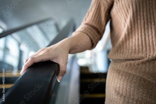 Fotografiet Hand of young woman touching the escalator during Coronavirus pandemic,risk of c