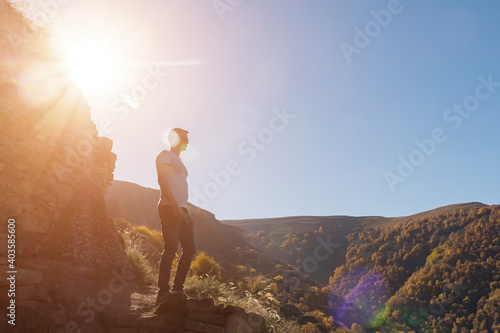 Canvas Print man on the background of a yellow forest on a mountainside on a clear day, sunlight, sun glare