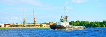 A Tug Boat Sailing Against Port Cranes In A Port In Latvia, Baltic Sea. Nautical Vessel, Freight Transportation, Global Communications, Industry, Commerce