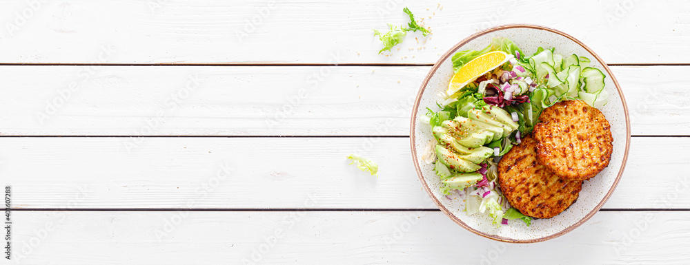 Fototapeta Buddha bowl dish with grilled chicken burgers, cucumbers, avocado and fresh lettuce salad for lunch, top view. Banner