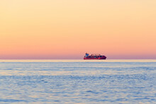 Container Cargo Ship On The Horizon At Sunset.