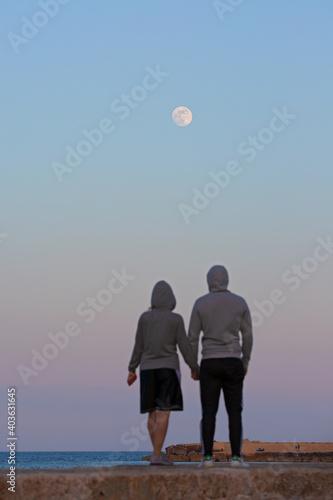 Fotomural Innamorati guardano la luna tenendosi per mano