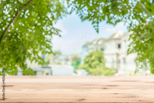 Obraz Green town home eco community blur background with wooden table forground space for products advertising template - fototapety do salonu