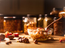 Farmer Honey Mixed With Nuts, Seeds In A Transparent Plate With Wooden Spoon, Jars, Walnuts, Dried Apricots On Rustic Wooden Kitchen Table. Still Life Photography