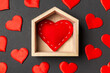Leinwandbild Motiv Close up of red heart in a wooden house decorated with small hearts on colorful background. Valentine's day. Home sweet home concept
