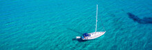 Yacht Anchoring In Crystal Clear Turquoise Water In Front Of The Tropical Island, Alternative Lifestyle, Living On A Boat. Aerial View Of Yacht At Anchor On Turquoise Water, Showing Luxury, Wealth.
