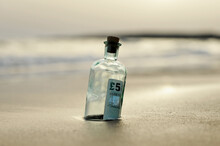 Bottle With Five Pound Note Inside Found In The Sand Of Beach, Currency Traffic And Tax Haven