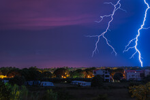 Two Large And Powerful Lighting Strikes Crossing Night Blue Sky And Hitting Urban Area With Houses And Campervans In Zaton, Croatia