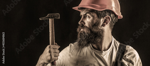 Obraz Handyman services. industry, technology, builder man, concept. Bearded man worker with beard, building helmet, hard hat. Hammer hammering. Builder in helmet, hammer, handyman - fototapety do salonu