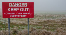 Bright Red Danger Keep Out Sign At The End Of An Airfield Grass Runway On A Foggy Morning