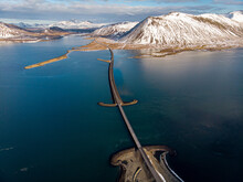A Drone Shot Of A Bridge With Snow Covered Mountains Near Grundarfjordur, West Iceland.
