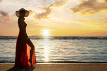 Young Woman Wearing Long Red Dress And Straw Hat Standing On Sand Beach At Sea Shore Enjoying View Of Rising Sun In Early Summer Morning.