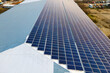 Aerial view of surface of blue photovoltaic solar panels mounted on building roof for producing clean ecological electricity. Production of renewable energy concept.