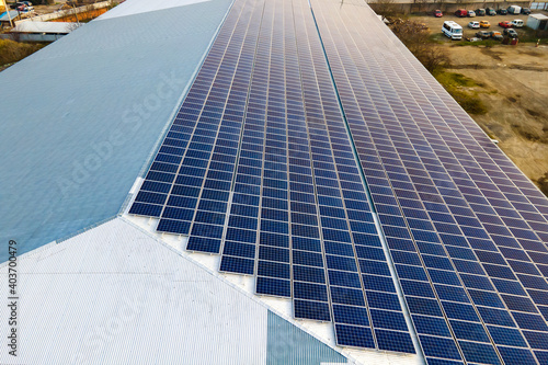 Obraz Aerial view of surface of blue photovoltaic solar panels mounted on building roof for producing clean ecological electricity. Production of renewable energy concept. - fototapety do salonu