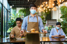 Portrait Attractive Asian Waitress Wear Face Mask And Face Shield Holding Food Tray To Serving Meal To Customer With Custome In Background. New Normal Restaurant Concept..