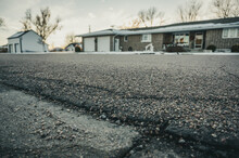 Low Angle Selective Focus On Asphalt Overlay Paving On Top Of A Concrete Base Of A Residential Street