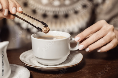 Obraz Woman puts a piece of brown cane sugar in a mug of coffee. The concept of healthy eating and excess of glucose and fast carbohydrates - fototapety do salonu